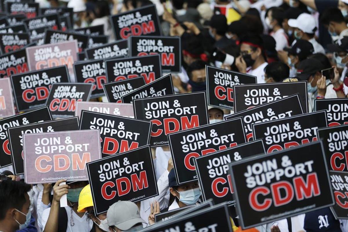 Manifestantes en Birmania muestran carteles que piden a los ciudadanos que se unan al movimiento de desobediencia civil (CDM, Civil Disobedience Movement).