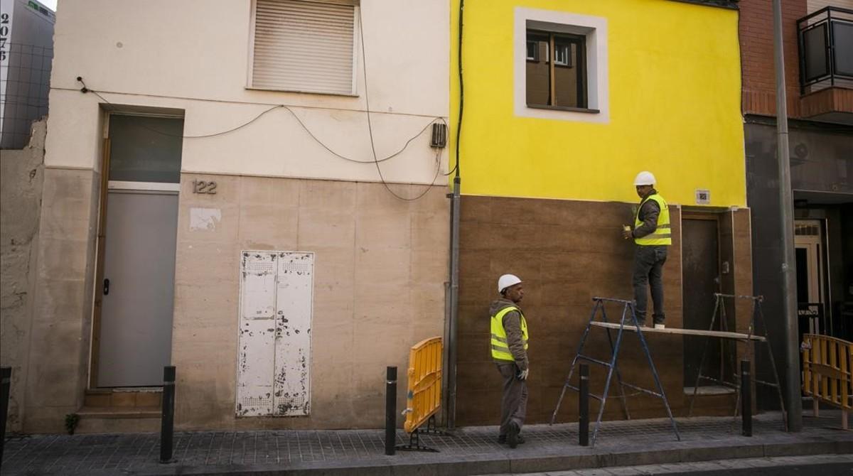 Albañiles dan los últimos retoques en las obras de rehabilitación del 120 de la calle de Pirineus de Santa Coloma de Gramenet.