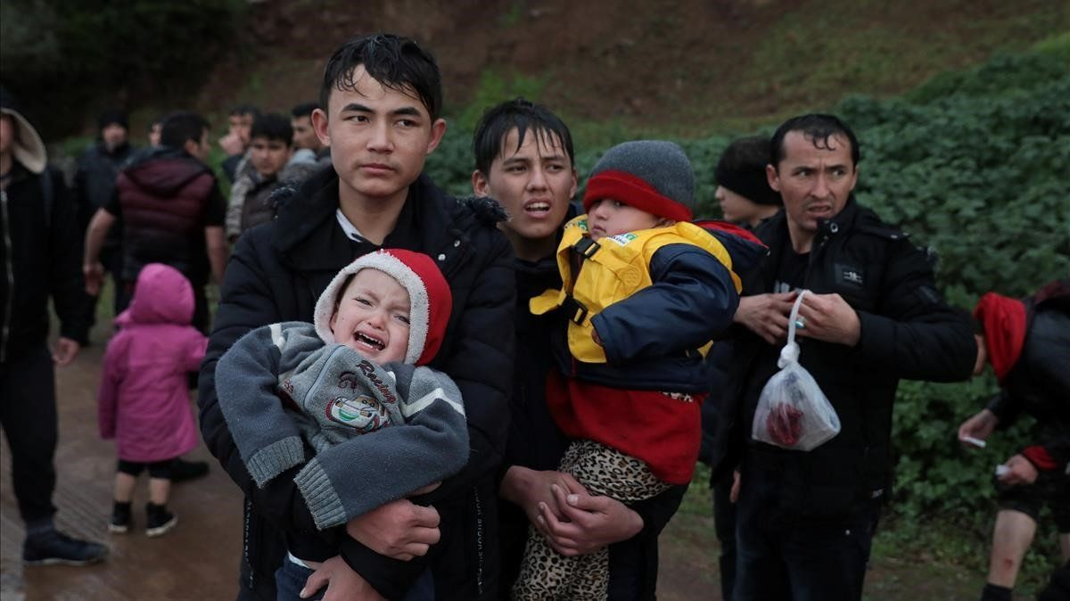 Migrantes caminan por una carretera de la isla de Lesbos tras llegar desde Turquía, este jueves.