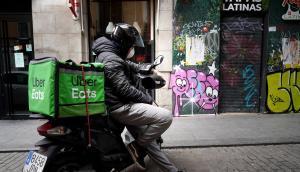 Un repartidor de UberEats espera un pedido en su motocicleta.