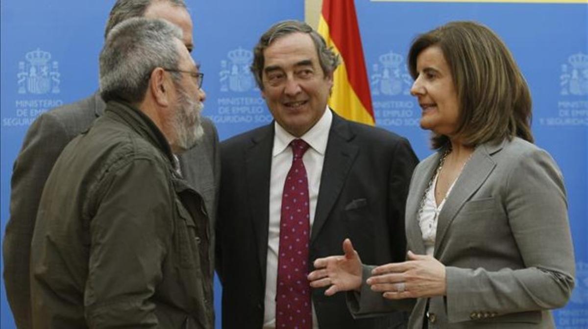 Báñez conversa con el líder de UGT, Cándido Méndez (izquierda) y el presidente de la patronal CEOE, Juan Rosell, el pasado abril.