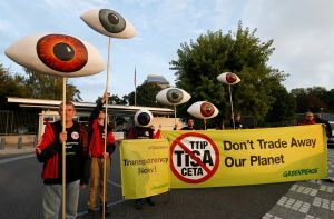 Greenpeace activists hold banners and giant eyes during a demonstration against the trade agreements TTIP, CETA and TiSA in front of the U.S. Mission in Geneva, Switzerland, September 20, 2016. REUTERS/Denis Balibouse
