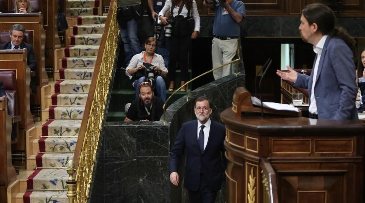 Mariano Rajoy vuelve a su escaño tras unos minutos fuera del hemiciclo mientras Pablo Iglesias habla en la tribuna.