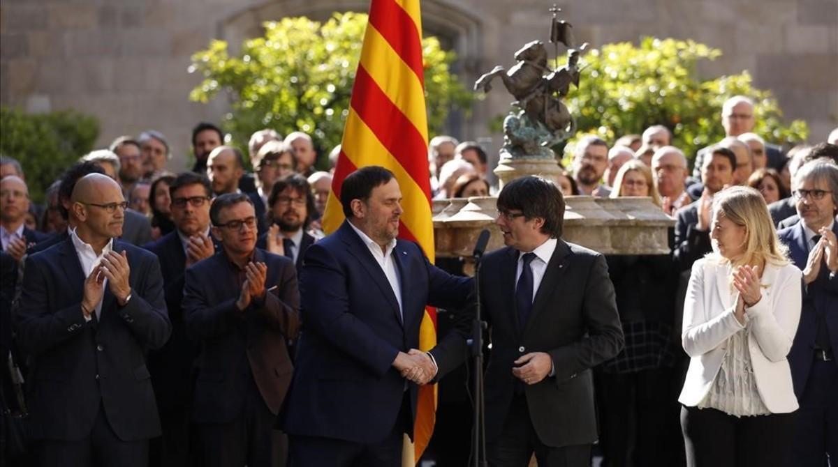 Oriol Junqueras y Carles Puigdemont se saludan en el acto solemne del Govern en apoyo al referéndum.