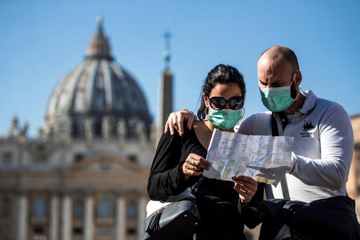 Una pareja de turistas con máscaras protectoras visita, en febrero pasado,la plaza de San Pedro, en el Vaticano.
