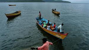 Pescadores y mujeres vuelven a sus casas en Port Blair, en el archipiélago de las Andamán, al que pertenece la isla Strait Island, donde vive la tribu Gran Andameneses.