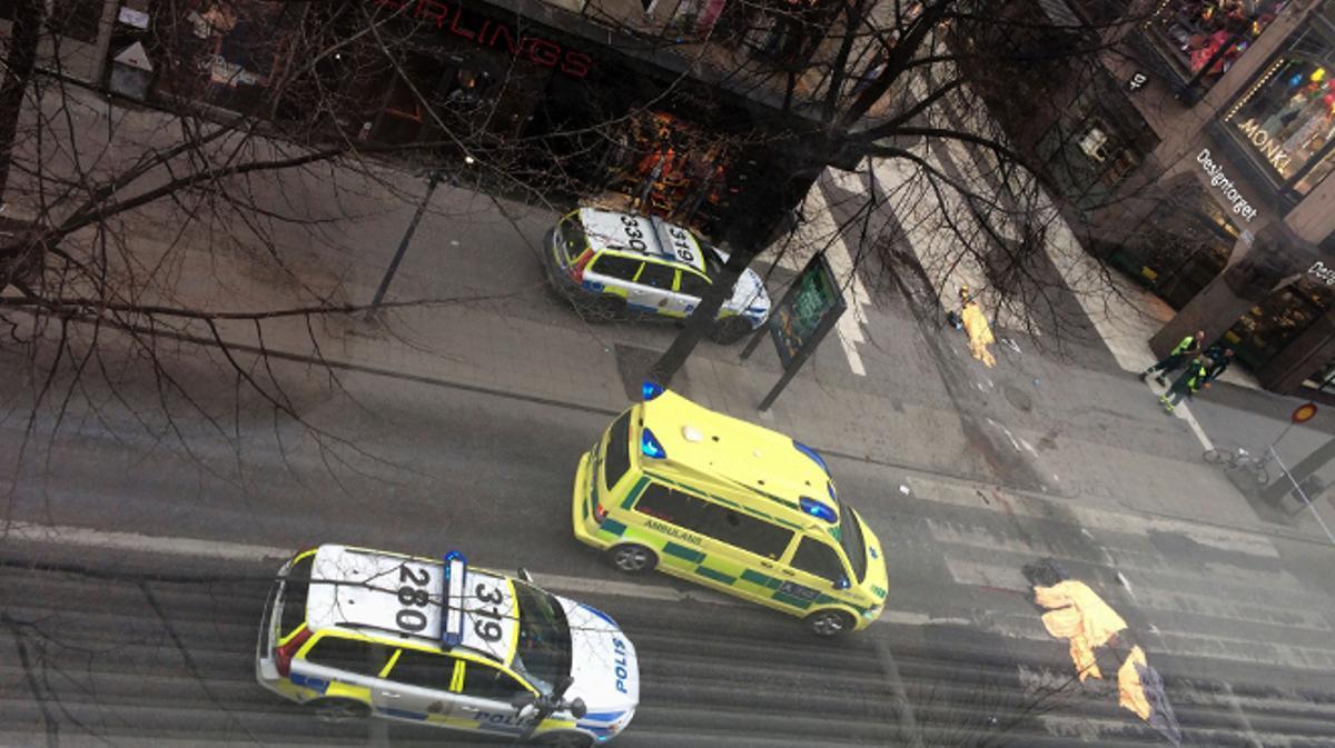 Una ambulancia ante los cuerpos de los tres muertos en un atentado con camión en Estocolmo.
