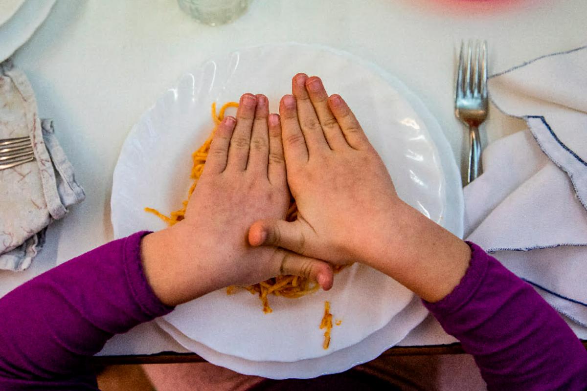 Un niño tapa con las manos su plato de pasta.