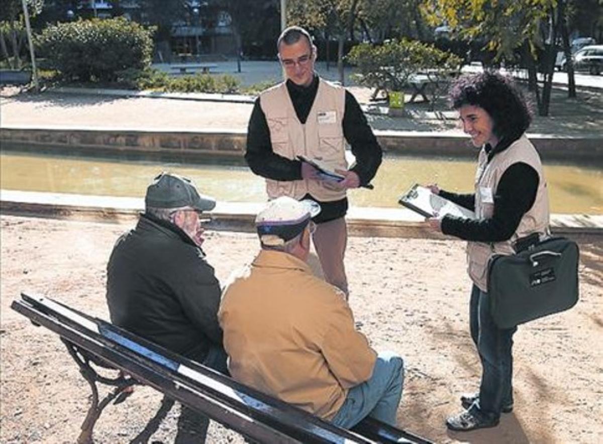 Informadores ambientales hablan con vecinos en la plaza de Les Corts.