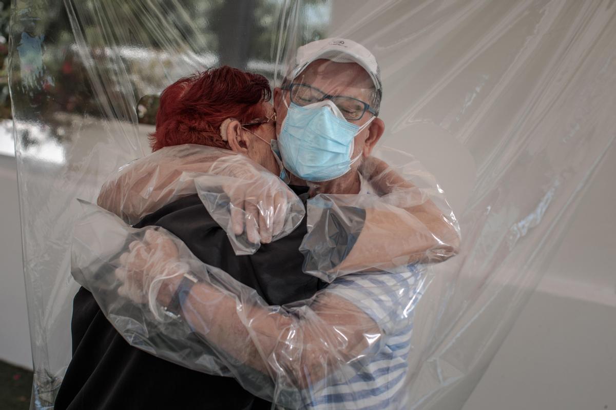 Una interna en una residencia de mayores abraza a su sobrino a través de un plástico habilitado para que los familiares se puedan dar su primer abrazo. Junio de 2020.