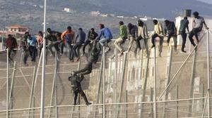 Un policía trata de hacer bajar a uno de los inmigrantes encaramados a la valla de Melilla.