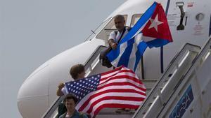 Dos pasajeros descienden de un avión en Santa Clara (Cuba) con sendas banderas de Estados Unidos y Cuba, en agosto de 2016.