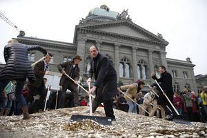 Activistes col·loquen cèntims a terra a les portes del Parlament a Berna, el dia 4 de setembre.
