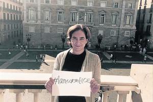 La alcaldesa de Barcelona, Ada Colau, en el balcón del ayuntamiento con un cartel contra el centro de internamiento de extranjeros (CIE), ayer.
