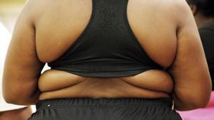 Una mujer con sobrepeso con un top deportivo.