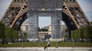 Una mujer camina con su compra frente a la TorreEiffel, en París.