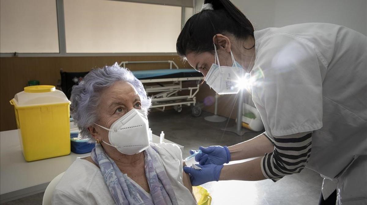 Una mujer de más de 80 años recibe la vacuna de Pfizer contra el covid en Barcelona.