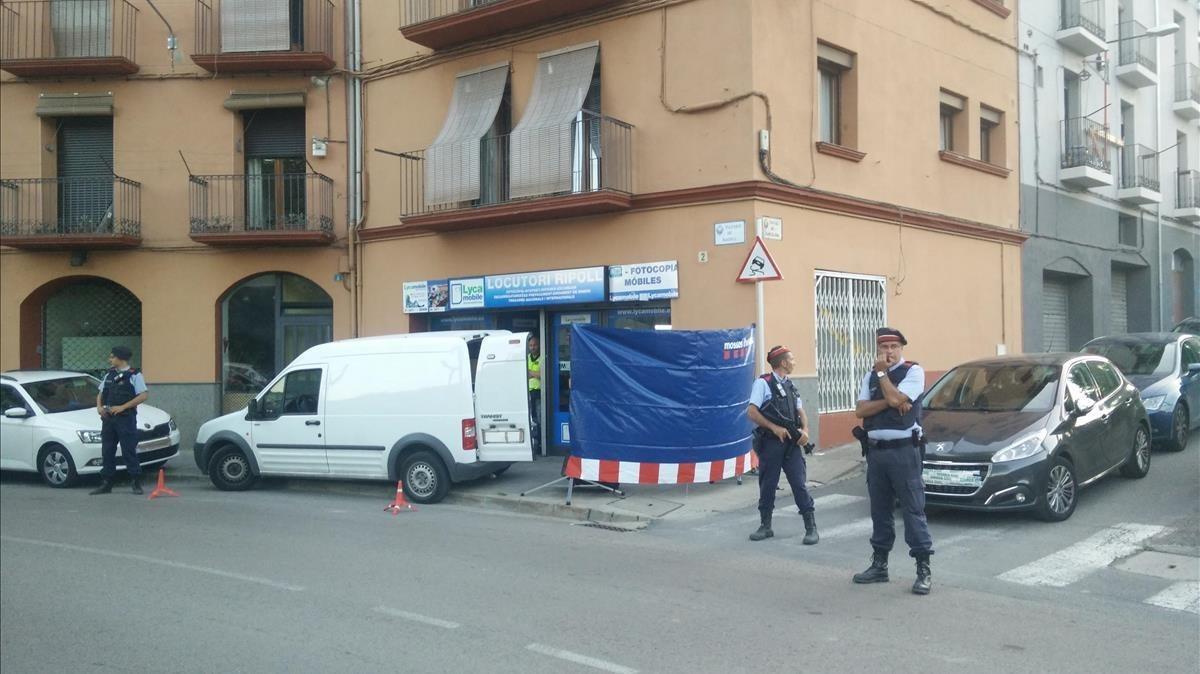 Agentes de los Mossos custodian la puerta de un locutorio de Ripoll registrado en relación con los atentados de Barcelona y Cambrils.