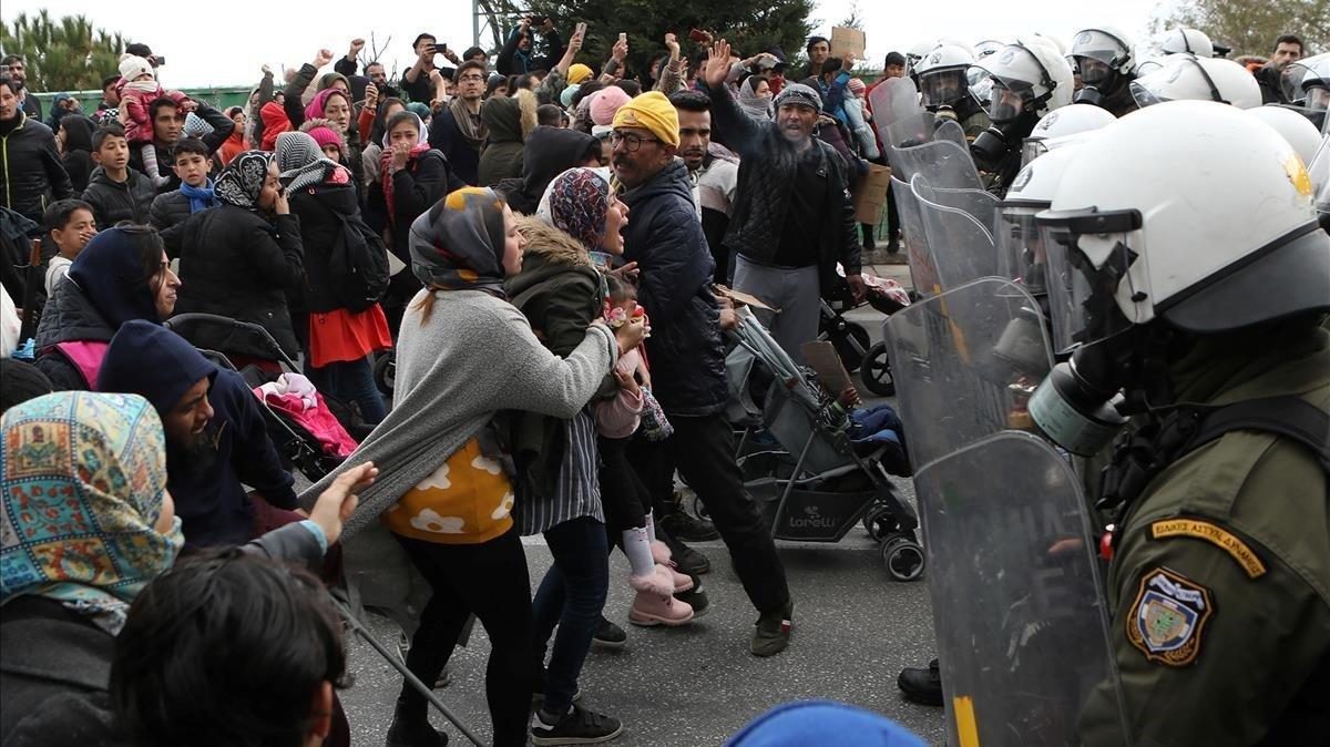 Un grupo de refugiados del campo de Moria se enfrenta a la Policía griega, este lunes.