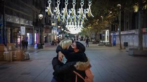 Dos amigas se dan un abrazo bajo las luces de Navidad del Portal de l'Àngel, en Barcelona.