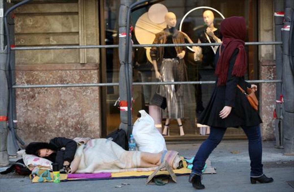 Un hombre duerme en la calle, en el paseo de Gràcia de Barcelona