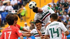 Edson Álvarez cabecea entre varios jugadores de México y Corea del Sur.