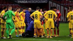 Piqué se lamenta de su grave lesión en la rodilla derecha rodeadode jugadores del Barça y del Atlético.
