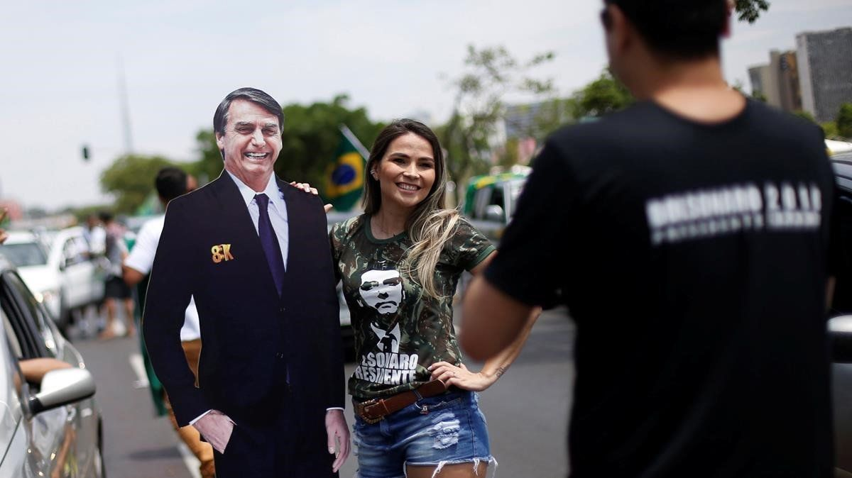 Una simpatizante posa junto a una fotografía tamaño natural deJair Bolsonaro.
