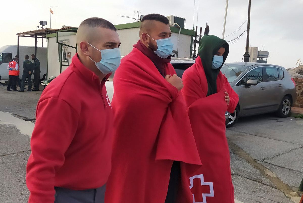 Dos inmigrantes marroquís son atendidos por un miembro de la Cruz Roja tras llegar a nado a Ceuta el pasado finde semana.