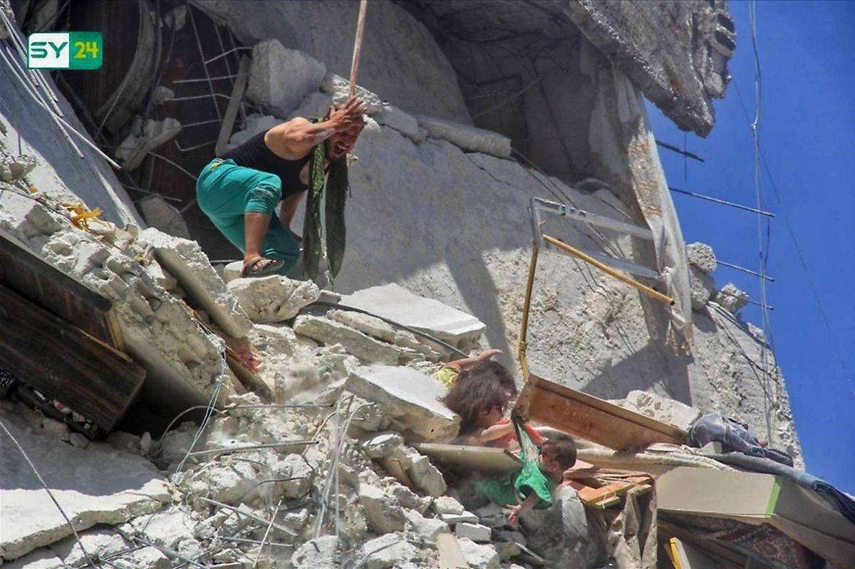 Una niña coge por la camiseta a su hermana pequeña mientras un hombre intenta ayudarlas tras el bombardeo de su edificio en el pueblo sirio de Ariha, este jueves.