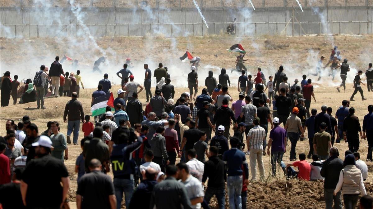 Manifestantes palestinos huyen de los gases lacrimógenos lanzados por fuerzas israelís, el pasado 15 de mayo en Gaza.