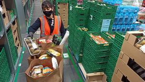 Trabajadora confecciona una cesta de la compra de Amazon Fresh.