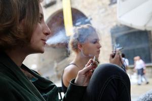 Dos mujeres jóvenes fuman sendos cigarrillos hechos con tabaco de liar,en el distrito de Ciutat Vella de Barcelona.
