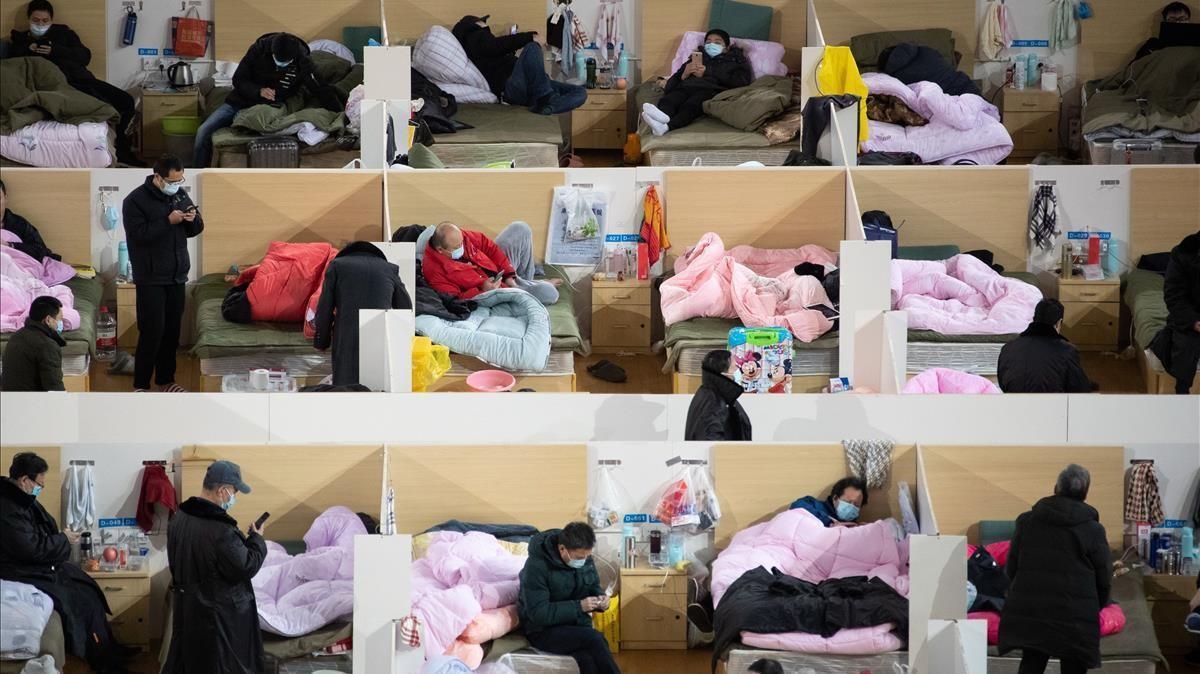 Pacientes de coronavirus guardan cama en el hospital de campaña levantado en Wuhan para atender el aluvión de urgencias, el 18 de febrero de 2020.