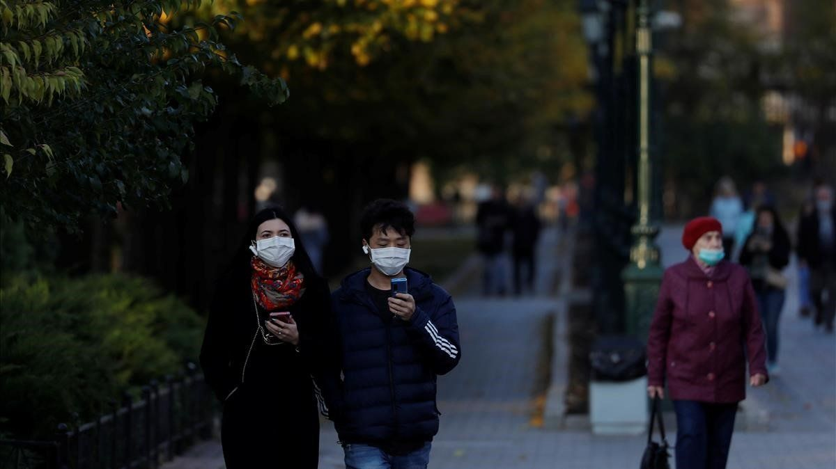 Varias personas con mascarilla pasena por un parque de Moscú, este martes.