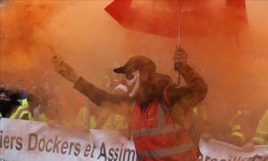 Un manifestante enciende una antorcha de humo durante la huelga contra las reformas del sistema de pensiones del Gobierno francés, este viernes, en Marsella.