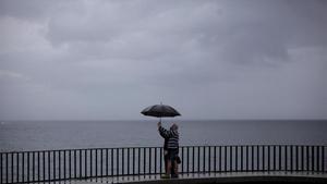 Dos personas se fotografía en el paseo marítimo de A Coruña en medio de una jornada lluviosa, este miércoles.