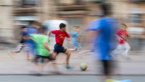 Unos chicos juegan a fútbol en una plaza del Poble Sec.