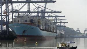 Un barco carga contenedores al lado del nuevo Canal de Panamá.