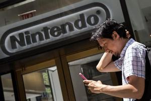 Un hombre juega al Pokémon Go con su móvil frente a la sede de Nintendo en Nueva York, el lunes.