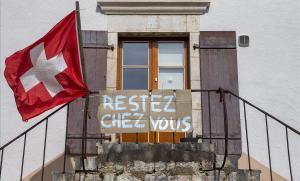 Un ciudadano de Ginebra cuelga un letrero en francés pidiendo que la gente se quede en casa.