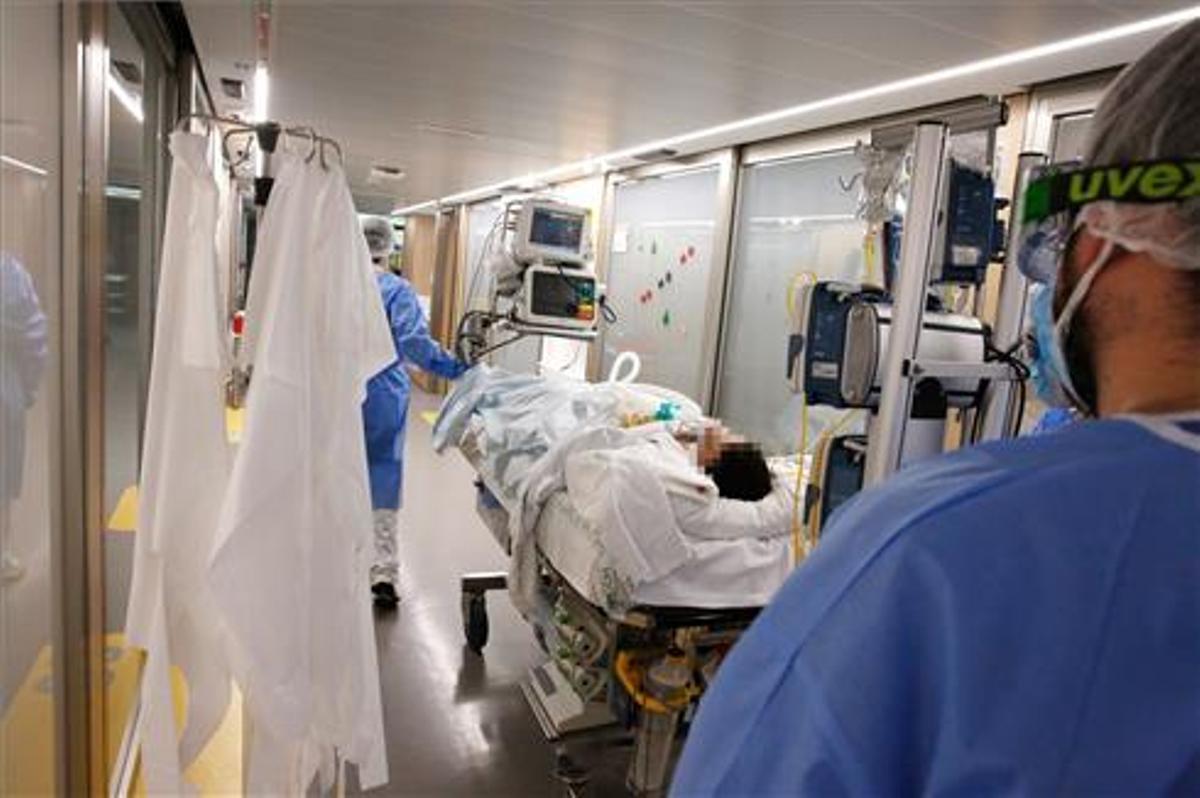 Unos enfermeros trasladan a un enfermo de covid en el Hospital Clínic de Barcelona.