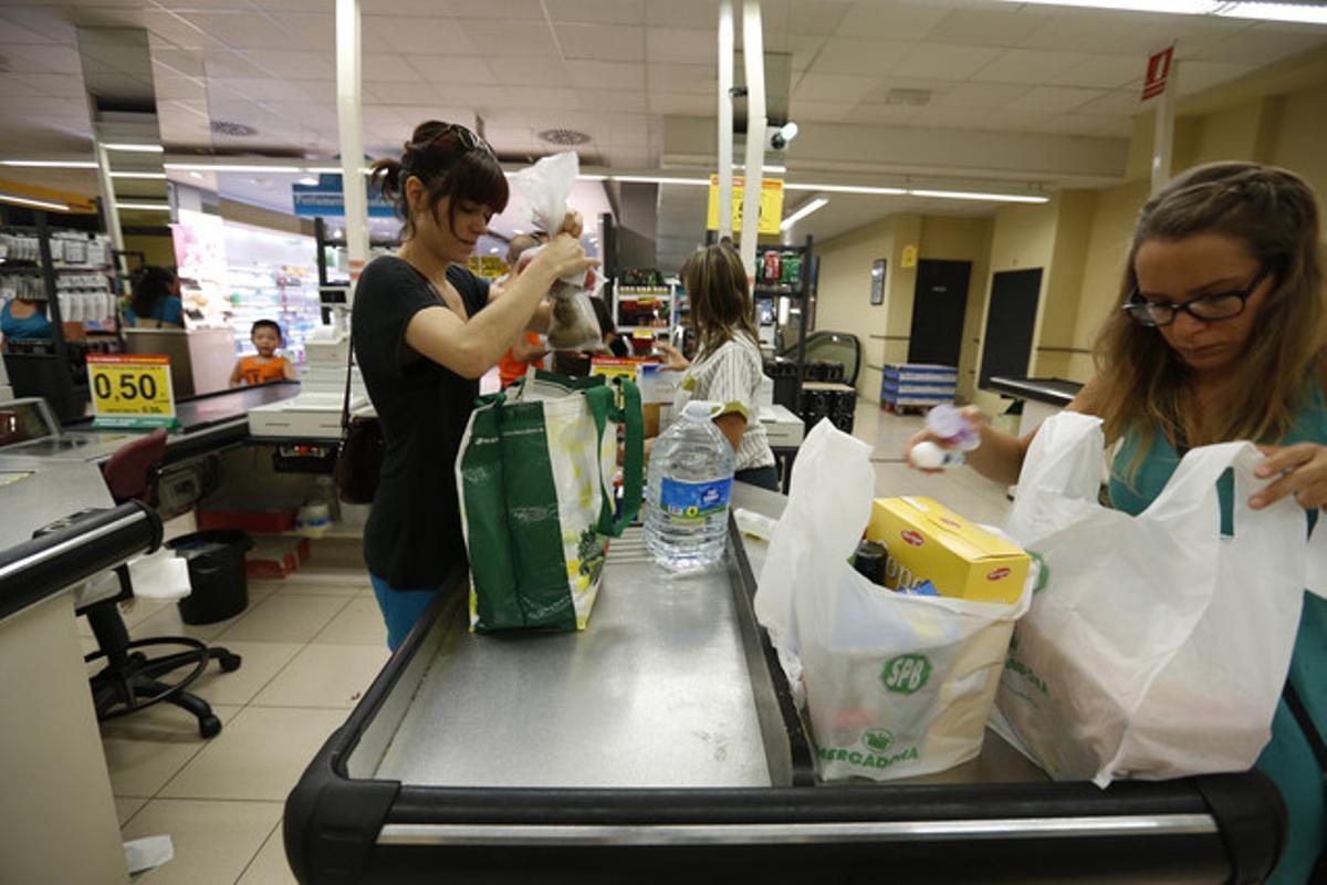Una clienta con una bolsa ecológica y otra, con bolsas de plástico, en un supermercado.