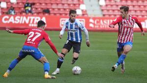 Embarba intenta escaparse de dos jugadores del Sporting.