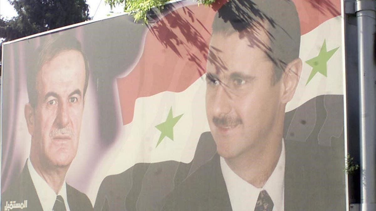 Un cartel con la imagen de Hafez y Bashar el Asad en Damasco, en el 2003.