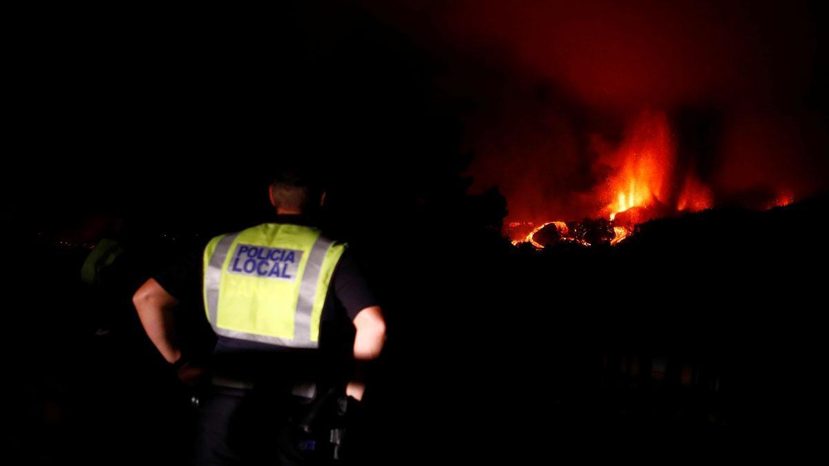 Un agente de la policía local sigue la erupción del volcán de La Palma en la distancia.