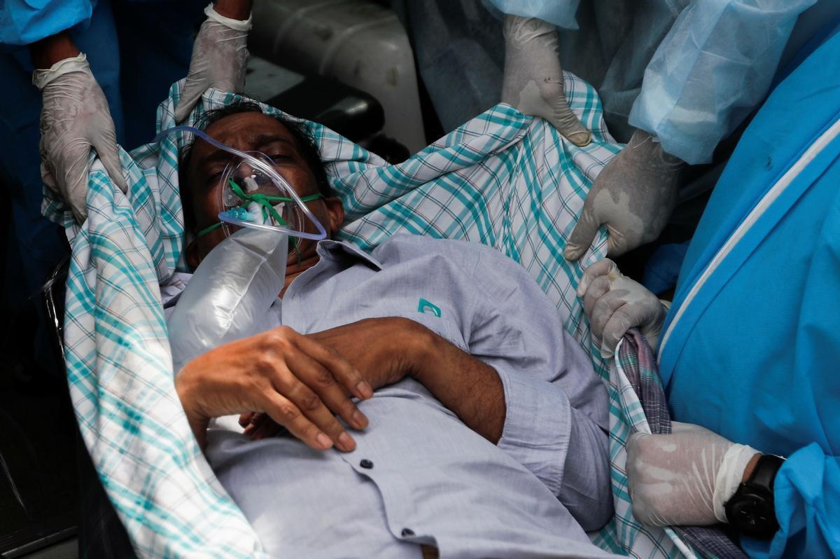 Un enfermo de covid es evacuado del hospital indio incendiado este viernes.