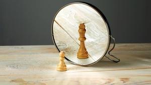 Peón de ajedrez frente al espejo.