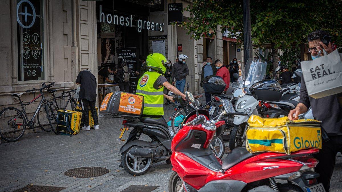 Repartidores de diferentes plataformas digitales aparcan sus vehículos frente a un local de comida rápida.
