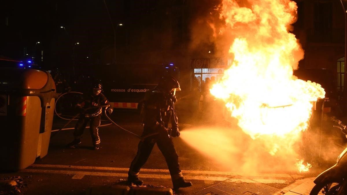 Bomberos apagan un contenedor en llamas en las protestas de los manifestantes contra un acto de Vox.